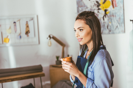 beautiful seamstress standing and holding cup of tea