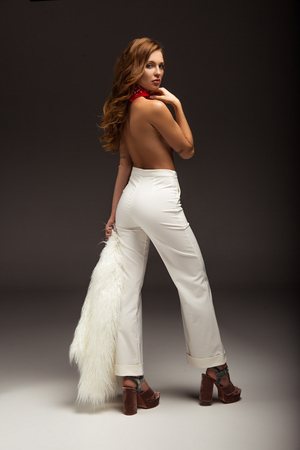 sexy woman with naked back in white trousers looking over shoulder Stok Fotoğraf