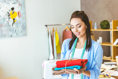 smiling seamstress holding stack of colored fabric