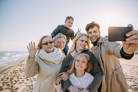 multigenerational family taking selfie on smartphone at seaside Stockfoto