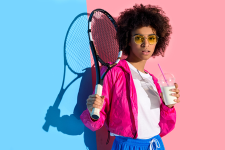 Young bright african american girl holding tennis racket and plastic cup with drink on pink and blue background Stock Photo
