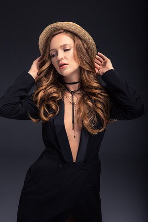 sexy woman posing in black jacket and straw hat isolated on gray