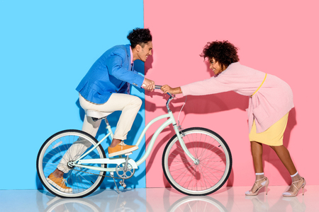 Happy couple having fun with bicycle on pink and blue background Stock fotó