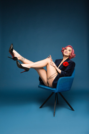 beautiful tattoed pin up girl in jacket with boutonniere posing on armchair infront of blue background Фото со стока