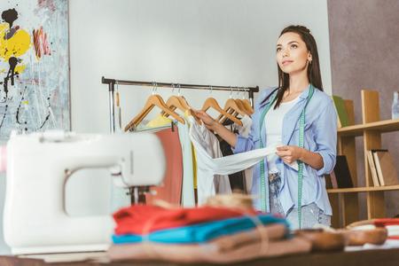 seamstress holding shirt at hanger and looking up
