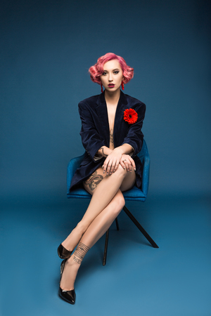 pretty pin up girl in jacket with boutonniere sitting on armchair infront of blue background