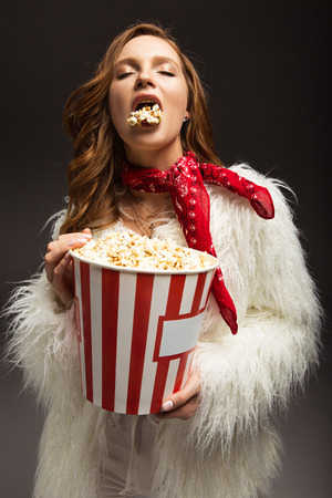 woman with closed eyes eating popcorn from box