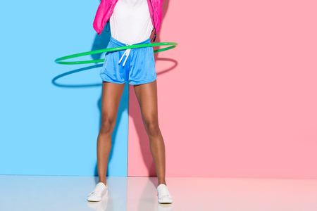 low section of  woman posing while exersizing with hoop on pink and blue background