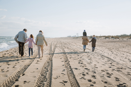 big multigenerational family walking together on seashore