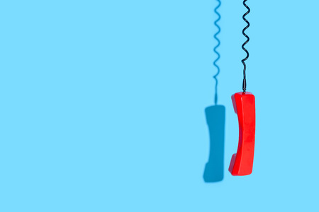 View of old telephone handset on blue background