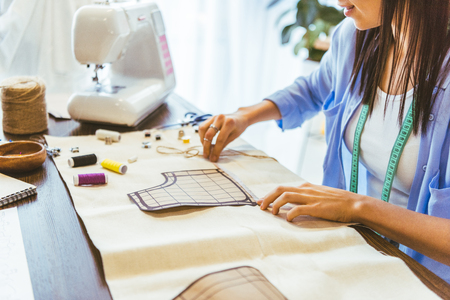 cropped image of smiling seamstress measuring pattern at table Stock Photo