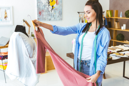 smiling tailor looking at pink dress in working room