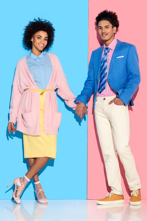 Young african amercian smiling girl and guy holding hands on pink and blue background