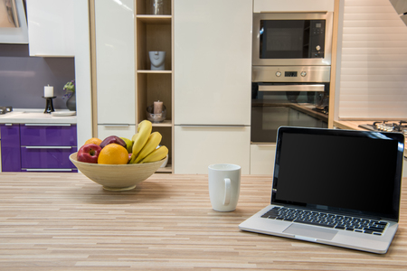 cozy modern kitchen interior with laptop and fruits in bowl