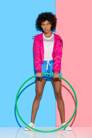 Woman in sportswear standing with hoop on pink and blue background Stock Photo