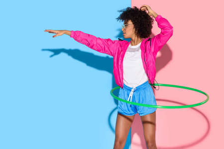 Sporty woman posing while exersizing with hoop on pink and blue background Stock Photo