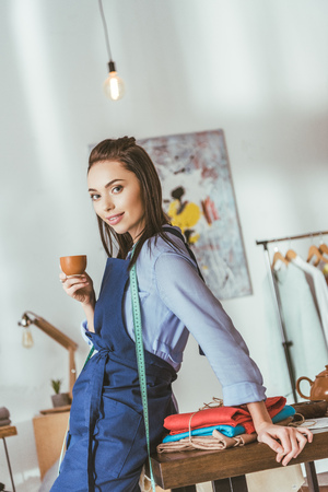 attractive seamstress leaning on table, holding cup of tea and looking at camera