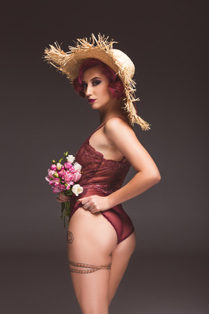 attractive tattoed pin up girl in lingerie and straw hat posing with flowers infront of grey background