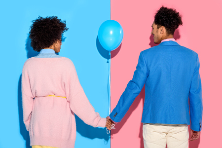 Rear view of couple holding hands with air balloon on pink and blue background 版權商用圖片