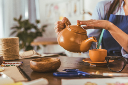 cropped image of seamstress pouring tea in cup during lunch