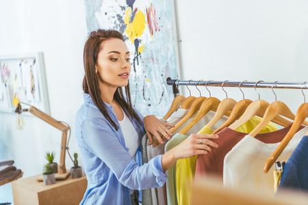 schöner Designer, der Kleidung auf Kleiderbügeln betrachtet Standard-Bild