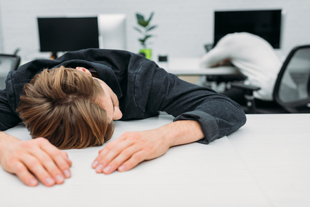 overworked young manager sleeping on work at modern office