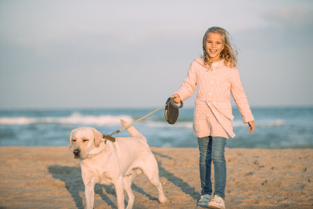kid walking with labrador dog on leash at seaside