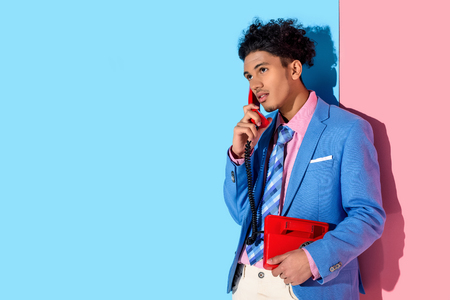 handsome man using handset of retro phone on pink and blue background Stock Photo