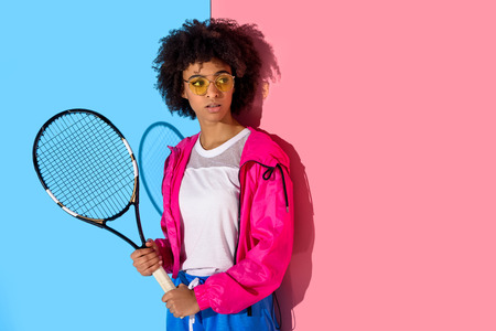 Young bright african american girl with tennis racket on pink and blue background Stock Photo