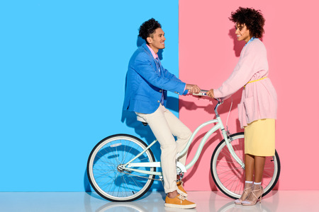 lovely young couple hugging each other on pink and blue background Stock fotó