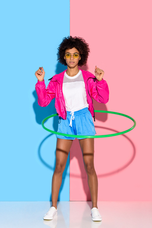 Sporty woman posing while exersizing with hoop and looking at camera on pink and blue background