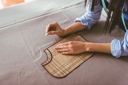 cropped image of seamstress making pattern with piece of chalk on fabric