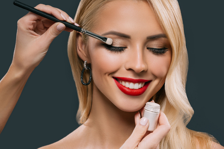 beautiful blonde woman applying glamorous makeup with eyeshadows, isolated on grey Stock Photo