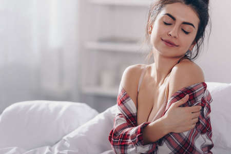 portrait of tender girl with closed eyes in checkered shirt sitting in bed in the morning