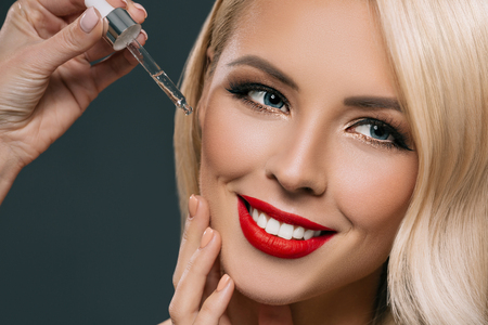 gorgeous blonde woman applying serum on her face, isolated on grey Stock Photo