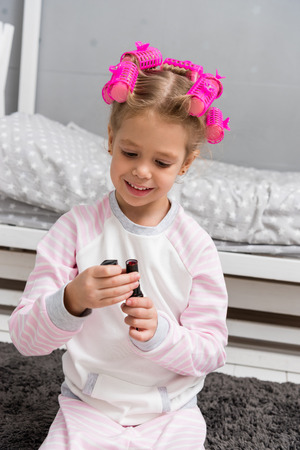 adorable little kid with hair rollers on head opening bottle with nail polish
