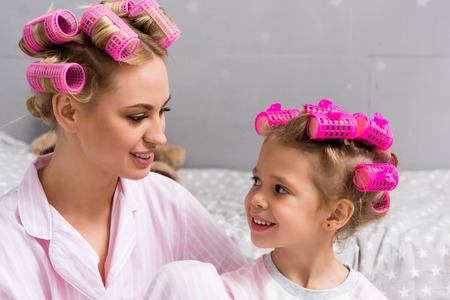 young beautiful mother and daughter with hair rollers on heads