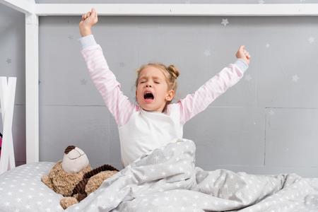 Adorable niño bostezando y estirándose mientras se despierta Foto de archivo