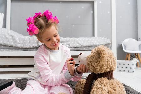 adorable little kid with hair rollers on head doing makeup for teddy bear