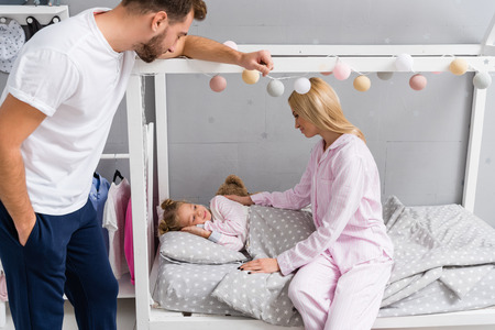 young parents talking to daughter while she lying in bed at kid bedroom