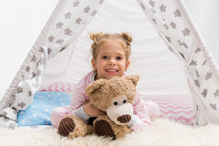adorable little kid with teddy bear lying on floor in handcrafted teepee Stock Photo