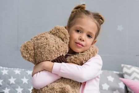 adorable little kid embracing her teddy bear and looking at camera Stock Photo