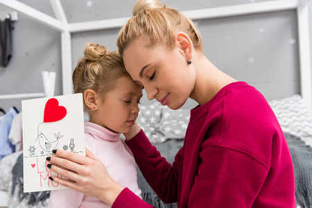 daughter presenting greeting card for mother on mothers day