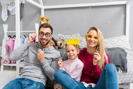 happy young family with masquerade crowns and eyeglasses sitting in kid bedroom