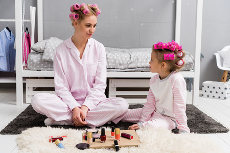 mother and daughter in pajamas with hair rollers on head sitting on floor