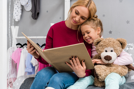mother and daughter sitting on bed and reading book together