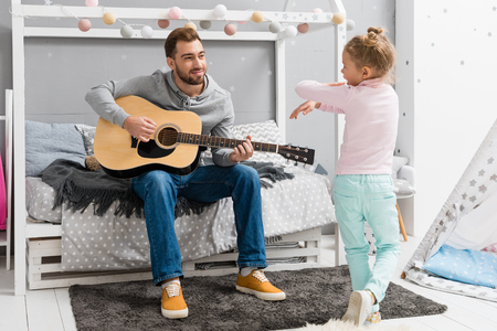 happy father playing guitar for daughter in bedroom while she dancing in front of him Stock Photo