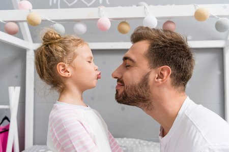 adorable little daughter kissing father with closed eyes