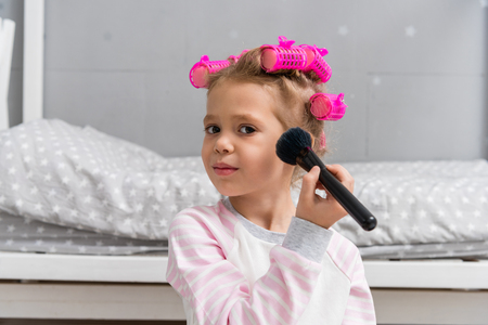 adorable little kid with hair rollers on head doing makeup with brush Zdjęcie Seryjne