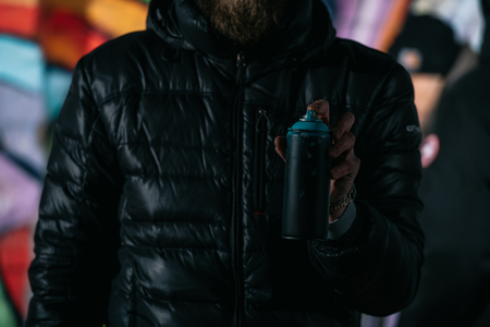 cropped view of man holding can with aerosol paint at night 写真素材